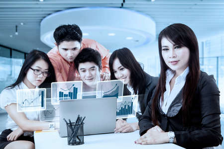 internet marketing: Young businesswoman smiling at the camera with her partners looking at virtual financial graph on the laptop, shot in the office Stock Photo