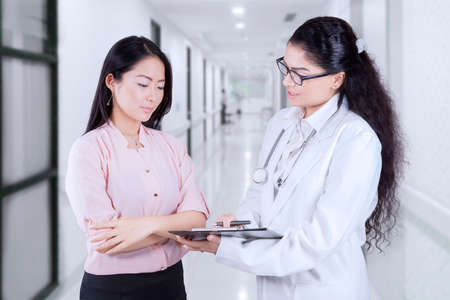 consultant: Asian doctor with stethoscope holding clipboard and explaining diagnosis to patient while patient looking at clipboard in the corridor hospital