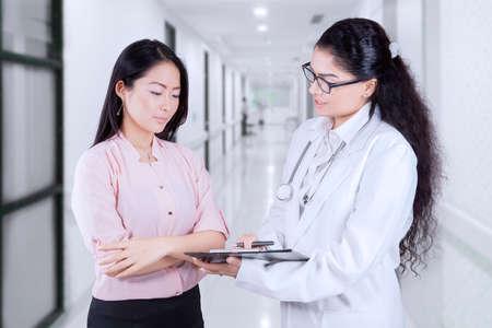 recetas medicas: Doctor asiático con el estetoscopio celebración portapapeles y explicar el diagnóstico de paciente mientras el paciente mira el sujetapapeles en el pasillo del hospital Foto de archivo