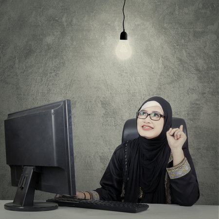 woman  glasses: Portrait of Arab business woman wearing glasses sitting and thinking of idea with under bright light bulb Stock Photo