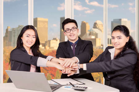 cohesiveness: Image of a multi ethnic business people making pile of hands in the office while smiling and looking at the camera with autumn background on the window