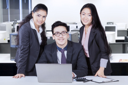 office tool: Three entrepreneurs smiling and looking at the camera after working together with laptop and office tool on the table