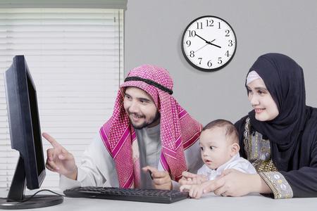 usando computadora: Retrato de la familia feliz de Oriente Medio que se sienta y que usa el ordenador para compras en línea, mientras que sostiene la tarjeta de crédito en la oficina