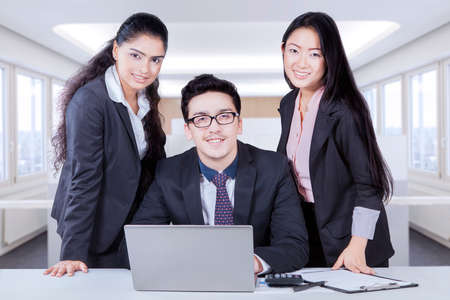 office tool: Portrait of young business looking and smiling at the camera with laptop and office tool on the table