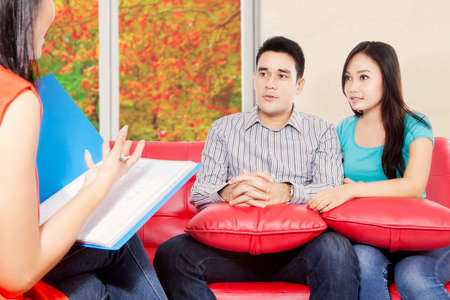 young wife: Portrait of husband and wife sitting in the red sofa and holding pillow while  psychiatrist giving motivation for young couple, autumn on the window