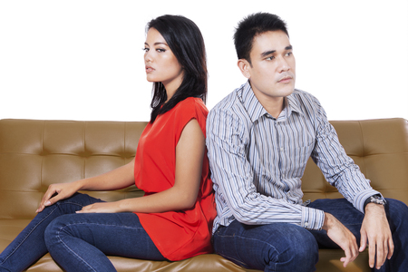 argument from love: Angry couple sitting sitting opposite each other on the brown sofa, isolated on the white background