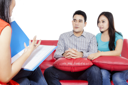red couch: Young couple sitting on the red couch and consulting with psychiatrist, isolated on the white background Stock Photo