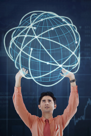financial symbol: Asian businessman holding a virtual globe with internet connection symbol and financial graph background Stock Photo