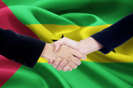 Picture of business handshake with two worker hands, shaking hands in front of a national flag of Sao Tome and Principe Stock Photo