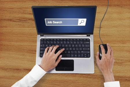 hand job: Picture of businessperson hand using laptop computer and mouse with job search text on the screen Stock Photo