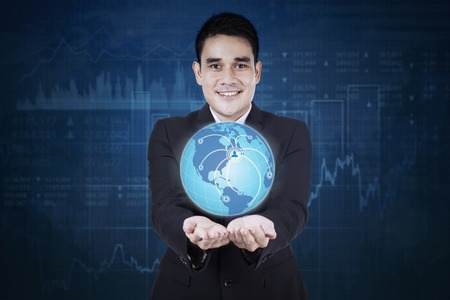 financial globe: Image of a young Asian businessman holding a globe with social network symbol and financial graph background.