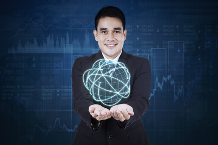 financial globe: Young businessman holding holding a globe with internet connection sign and financial graph background