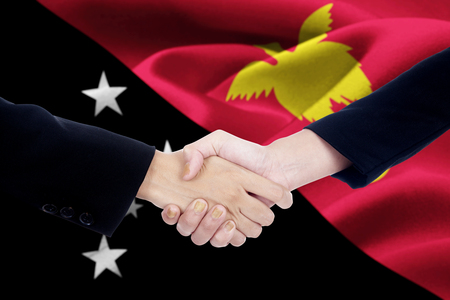 new guinea: Image of business handshake with two people hands, shaking hands in front of a national flag of Papua New Guinea Archivio Fotografico