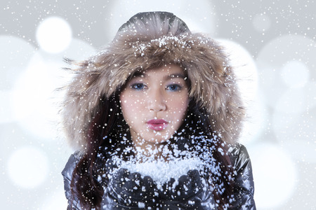 japanese people: Attractive teenage girl wearing winter jacket and blowing snow on her palms with bokeh background