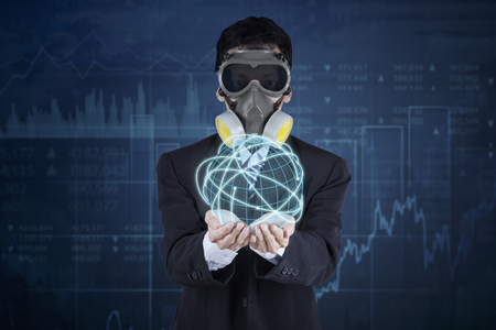financial globe: Businessperson wearing a gas mask and holding a globe with internet connection symbol and financial statistic background