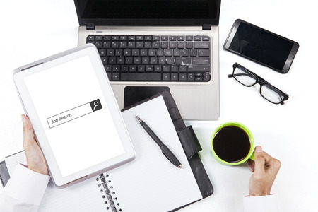hand job: Concept of Job Search. Businessman hand holding a digital tablet with job search bar on the screen. Shot with laptop, mobile phone, coffee, and planner book on desk