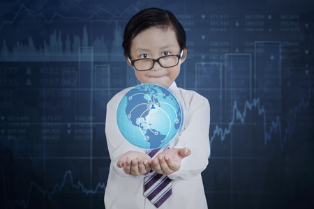 financial globe: Little businessman wearing glasses and holding a globe with social network icon and financial statistic background. Elements of this image furnished by NASA Stock Photo