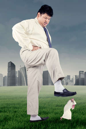 downtrodden: Overweight businessman trampling down his rival on the meadow, shot outdoors