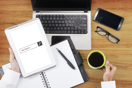 Image of businessman hand holding digital tablet with job search bar on the screen. Shot with laptop, cellphone, book planner, and coffee on desk Stock Photo