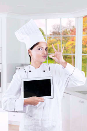 gourmet kitchen: Female gourmet shows a deliciousness gesture while holding a digital tablet in the kitchen with autumn background on the window