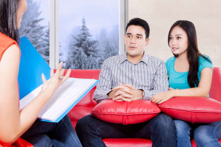 psychiatry: Young couple sitting on the red couch and listening while psychiatry explaining their problem. winter on the window