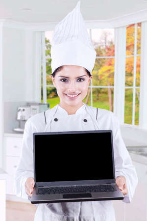 gourmet kitchen: Female gourmet wearing uniform in the kitchen and showing empty laptop screen with autumn background on the window