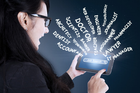 search searching: Young businesswoman touching a digital tablet screen and searching jobs. Concept of Job Search