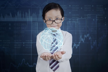financial globe: Little boy wearing glasses and holding a globe with internet connection symbol and financial statistic background