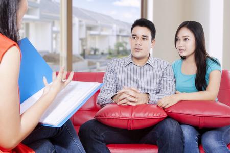 Mąż i żona konsultacji z ich problemu przez psychiatrę, siedząc na czerwonej kanapie w domu