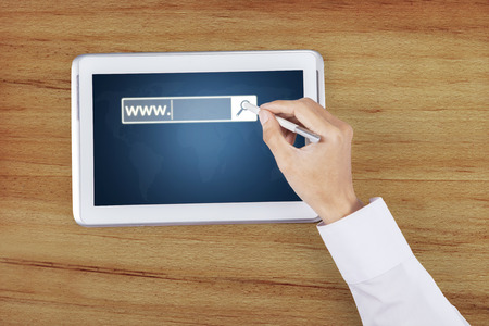 stylus pen: Businessman hand touching a digital tablet screen with a stylus pen and www text on the screen