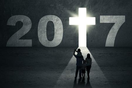familia cristiana: Año Nuevo 2017 viene concepto. Silueta de una familia mirando a una puerta en forma de un símbolo de la cruz luminosa, con número 2017