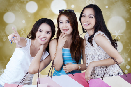 Three attractive teenage girls carrying shopping bags and pointing at something, shot with bokeh background Stock Photo