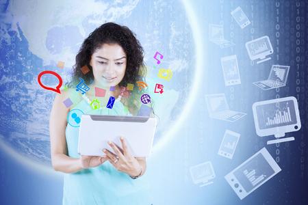 obra social: Mujer joven que usa una tableta digital con iconos de redes sociales y el fondo del globo. Los elementos de esta imagen proporcionada por la NASA