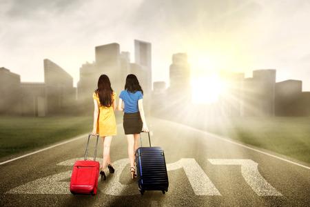 mujer con maleta: Dos muchachas que recorren en la carretera que lleven la maleta con los números 2017 y la luz del sol