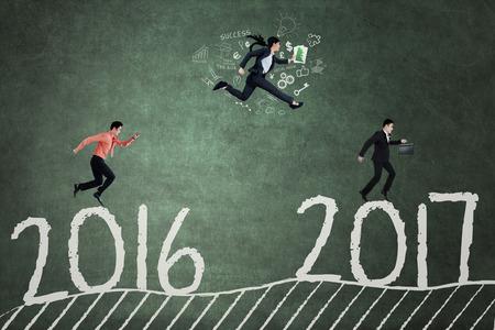 jovenes empresarios: Concepto de la competencia empresarial en 2017. Tres jóvenes empresarios compiten para llegar a 2017 por correr y saltar en la pizarra