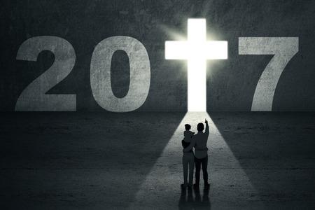 familia cristiana: Año Nuevo 2017 viene concepto. Silueta de una familia que busca en el número 2017 con un símbolo de la cruz luminosa en forma de una puerta