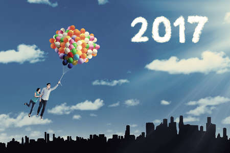 married couples: Image of two young couple flying together on the sky with colorful balloons and cloud shaped number 2017 Stock Photo