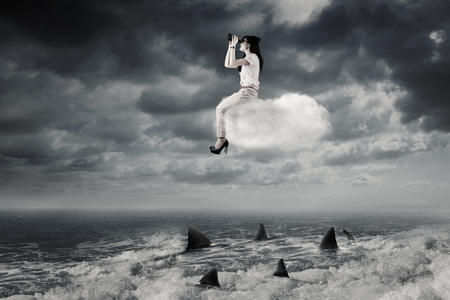 Young Asian businesswoman sitting on the cloud and looking through binoculars above dangerous sharks on the sea