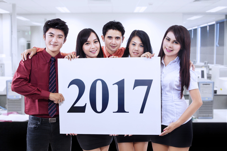happy worker: Group of Asian businesspeople standing in the office while holding a billboard with number 2017 Stock Photo