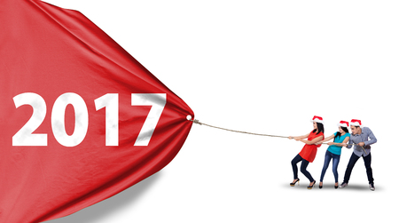 pulling rope: Group of Asian people wearing christmas hat and pulling a red banner with number 2017, isolated on white background