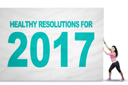 weight loss plan: Image of a fit Indian woman pulling a big flag with text of healthy resolution and number 2017