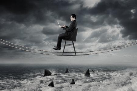 Jeune homme d'affaires travaillant avec un ordinateur portable sur la corde tout en restant assis sur la chaise au-dessus de requins dangereux sur la mer Banque d'images - 64063777