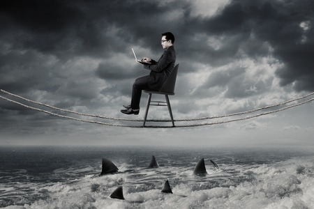 Jonge zakenman werken met laptop op het touw terwijl het zitten op de stoel boven de gevaarlijke haaien aan de zee Stockfoto