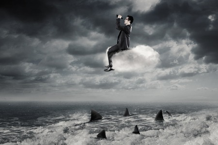 dangerous ideas: Young Asian businessman looking through binoculars while sitting on the cloud above dangerous sharks on the sea Stock Photo