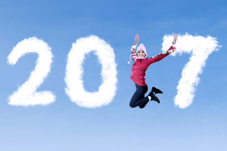 chinese hat: Attractive woman jumping on the blue sky while wearing winter clothes with clouds shaped number 2017