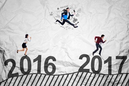 jovenes empresarios: Concepto de la competencia empresarial en 2017 con tres jóvenes empresarios de correr y saltar para competir hacia 2017