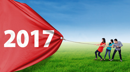 Young Asian people using a rope to pull a big banner with number 2017 on the meadow, shot outdoors
