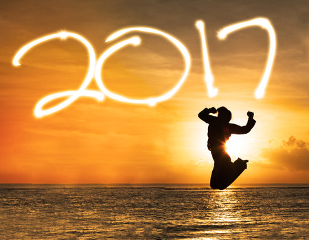 Concept of Happy New Year 2017. Silhouette of happy woman jumping on the beach with number 2017 Stock Photo