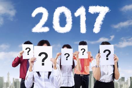 democracia: Imagen de las personas desconocidas que llevan a cabo signos de interrogación y los números en forma de nube de 2017, por el cielo Foto de archivo