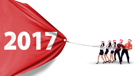 Group of young workers wearing christmas hat and pulling a big banner with number 2017, isolated on white background Stock Photo